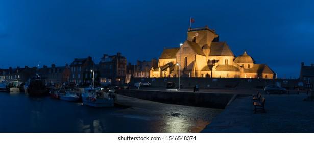 Barfleur, Manche / France - 16 August, 2016: the Saint Nicolas church and harbor in Barfleur nighttime view