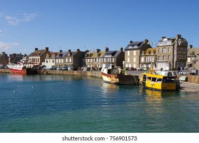 Barfleur, Normandy, France. 12 April 2012. Fishing harbour, boats and terraced seaside cottages on a sunny day.