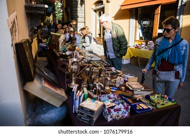 BARGA, ITALY - OCTOBER 8, 2017: People visit flea market in small ancient medieval touristic italian town, Lucca, Tuscany.