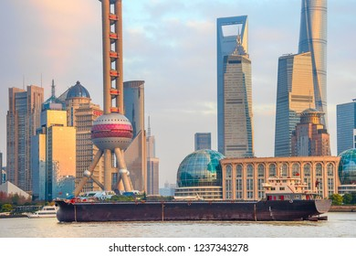 Barge by sunset Shanghai skyline with famous tv tower and skyscrapers of modern architecture, China