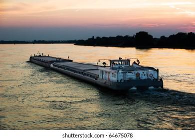 barge in Danube river, at evening sky