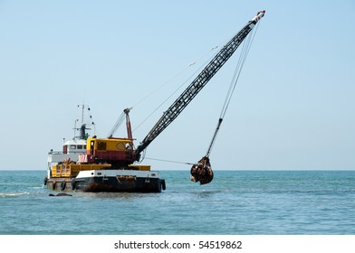 A barge is dredging a harbor removing stones and sand
