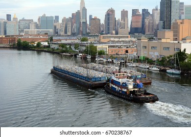 Barge Filled With Recycling Materials Being Pushed Through Newtown Creek and Manhattan Skyline