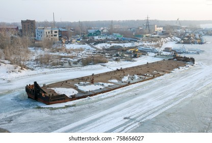 The barge frozen on ice on the river Samara, Russia