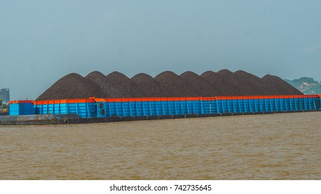 barge full loaded with black coal ready to transported through the river