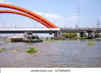 Barge hauling boulders under bridge on Saigon River, Vietnam.