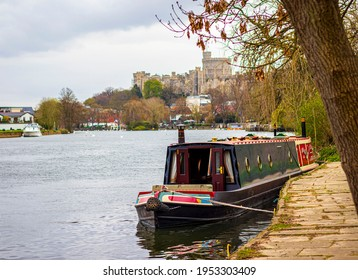 Barge moored on an Thames River ,Windsor castle in the background. The highlights of living on the boat.  Windsor 10 04 2021 United Kingdom