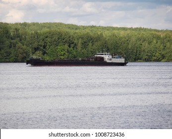 Barge & pusher tug boat on river. Vessel cargo tugboat barge transporting iron, coal to harbor for exporting along river. Tug boat hauls large barge down river to sea. Tug Boat or cargo transport ship