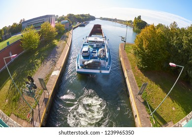 A barge is sailing on a canal in bright sunshine.