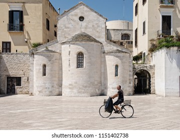 Bari, Italia - 30 Jul 2018: view of square and man going by bicycle on siesta time in the city Bari, Italia.Vallisa Church building on the Ferrarese square in Bari Apulia Italy