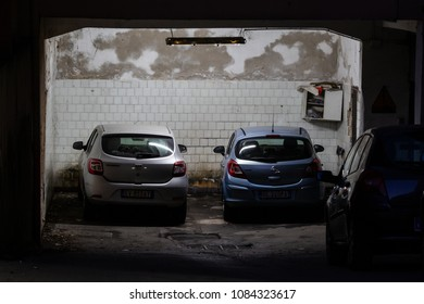Bari, Italy / 04 14 2018: An old parking lot or an abandoned garage at night, and two parked cars.