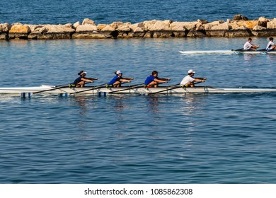 Bari, Italy - 04 21 2018: Saturday afternoon and canoe training on the sea, in the background of the coast of the city of Bari.