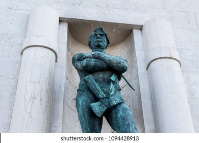 Bari, Italy - 04 21 2018: Two white columns and a statue. In the middle of a building a warrior with his arms folded and an axe on his side.