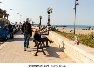 Bari, Italy - 04 21 2018: An old man sitting on a bench, boys set up surfboards, bystanders and street vendors on a sunny afternoon in the city.