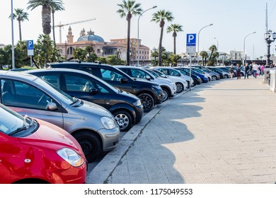 Bari, Italy - 04 21 2018: Numerous cars parked on the seafront in Bari, the capital of Puglia in southern Italy, in the background trees and the old Theater Margherita.