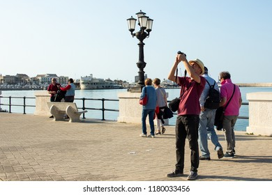 Bari, Italy - 04 21 2018: A tourist on the seafront of Bari, the capital of Puglia in southern Italy, working with his camera.