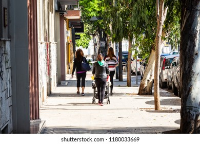 Bari, Italy - 04 22 2018: Mother and son stay together during a walk in the city on sunday morning. Woman push baby carriage for the streets.