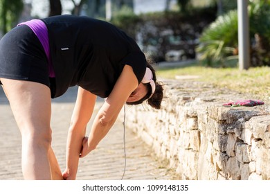 Bari, Italy - 04 25 2018: Jogging in the morning at the park. A girl gets ready doing stratching while listening to music.
