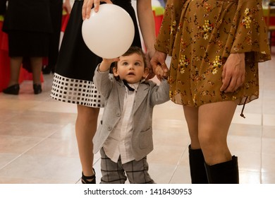 Bari, Italy - 04 25 2019: Sunday in an Italian restaurant. Birthday party for a small blue-eyed child dressed elegantly in a jacket, shirt and pants.