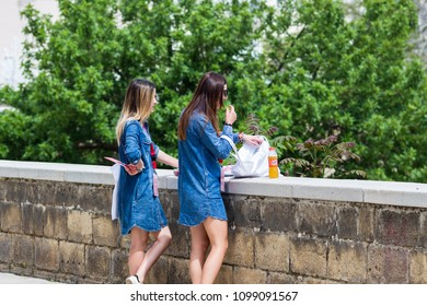 Bari, Italy - 04 29 2018: Two hostesses during a break from work, eat something for the wall of the city of Bari, in Italy.