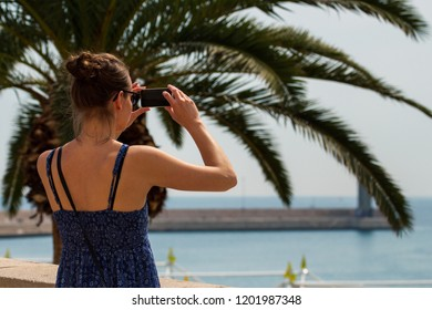 Bari, Italy - 04 29 2018: A young girl photographs the city pier from the top of the wall.