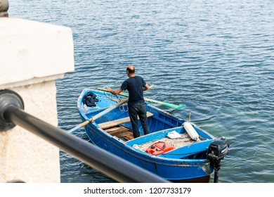 Bari, Italy - 04 29 2018: A fisherman rows to get closer to the pier