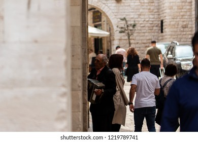 Bari, Italy - 04 29 2018: On the streets of the city. A homeless plays an accordion among the people.