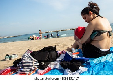 Bari, Italy - 05 01 2018: Spring on the beach. A girl with her son, families and a group of sportsmen at sea early in the morning.