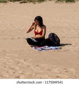 Bari, Italy - 05 01 2018: A girl in a red bikini, alone in a corner of the beach, reading a book.