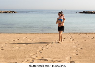 Bari, Italy - 05 01 2018: A mother with her son in her arms walks along the beach on the sand, in the early hours of a morning on a hot May day.