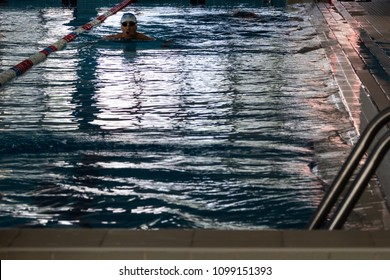 Bari, Italy - 05 13 2018: A swimmer trains alone inside an indoor pool in the city of Bari, Italy, in the morning.