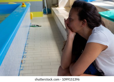 Bari, Italy - 05 13 2018: Profile portrait of a woman, inside a swimming pool in Bari, Italy, while observing a swimming course for children.