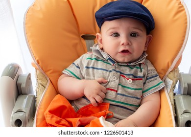 Bari, Italy - 05 25 2018: Morning at home. A newborn baby with a beret sitting on the seat.