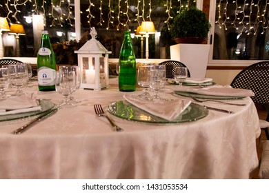 Bari, Italy - 07 27 2018: Birthday party in the evening in a restaurant in Bari, in southern Italy. One of the guest tables set for dinner is furnished with a lantern in the shape of a house.