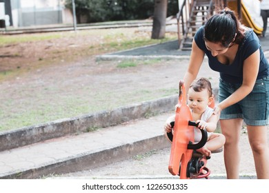 Bari, Italy - 09 06 2018: Morning at the city park. Mother and son play with a wooden horse.