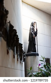 Bari, Italy - 10 21 2018: Statue of Saint Francis of Paola, founder of the Order of Minims, on the background of representations of Way of the cross