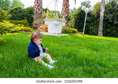 Bari, Italy - 10 21 2018: A newborn baby sitting on a green lawn on the background of a well and trees.