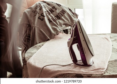 Bari, Italy - 10 28 2018: Morning cleaning at home. A woman is ironing some clothes on the table.