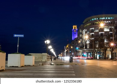 Bari, Italy - 11 11 2018: Night in the city of Bari, in Italy. Evening traffic on the background of one of the most important hotels.