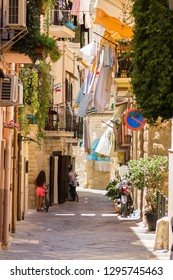 BARI, ITALY - JULY 11, 2018, View of a narrow street in the Italian city Bari, linen is dried in the street