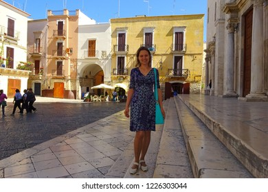 Bari, Italy - July, 2014: woman stands on  Square in old town of Bari, Italy. Bari is capital city of Metropolitan City of Bari and of Apulia region, on Adriatic Sea, in southern Italy