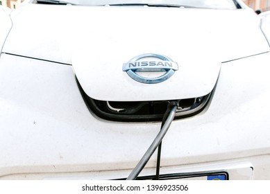 Bari, Italy - March 12, 2019: A 100% electric car from the Nissan brand is recharged on the street in a free recharge station by Enel in Italy.