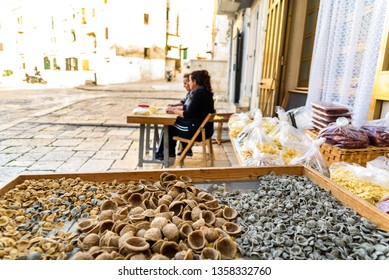 Bari, Italy - March 8, 2019: Artisan women preparing at the door of their house in the Italian city of Bari the traditional ear-shaped pasta, called orecchiette, made with flour and salt water.