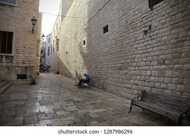 Bari, Italy-September 19, 2015: Man resting on a bench in old Bari.