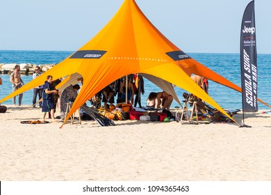 Bari/Italy - 04 21 2018: Group of person under a beach tent during the event of a wind surf school in the city of Bari, in the south of Italy.