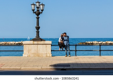 Bari/Italy - 04 21 2018: Tourists on vacation in the city of Bari. A boy and a girl take a selfie near the seafront on a spring afternoon.