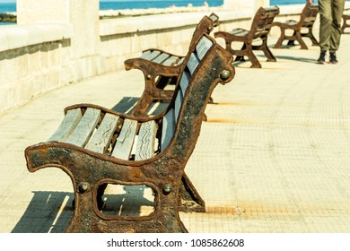 Bari/Italy - 04 21 2018: Walk along the seafront of Bari during the afternoon. Old benches, made of wood and iron, on the street.