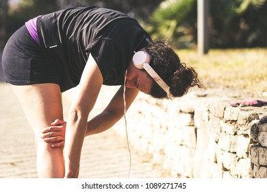Bari/Italy - 04 25 2018: Jogging in the morning at the park. A girl gets ready doing stratching while listening to music.