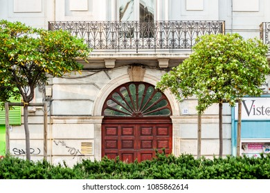 Bari/Italy - 04 25 2018: A wooden door with decorations in the middle of an old building and some trees.