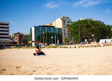 Bari/Italy - 05 01 2018: A girl in a red bikini, alone in a corner of the beach, reading a book.